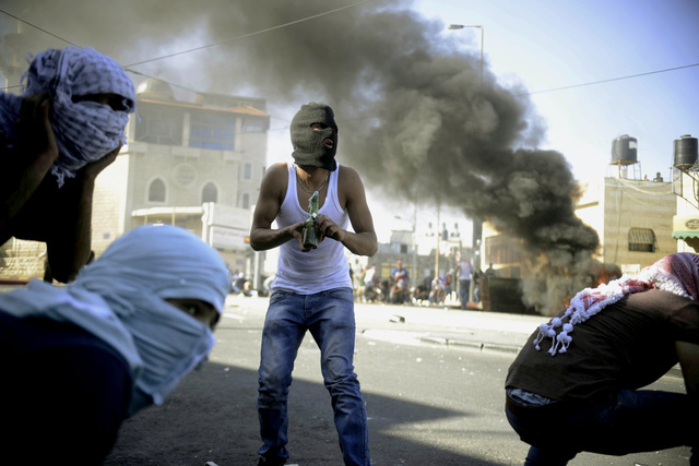 A Palestinian holds a Molotov cocktail during clashes with Israeli border police in Jerusalem on Wednesday, July 2, 2014. The suspected abduction of an Arab teen followed by the discovery of a bod ...