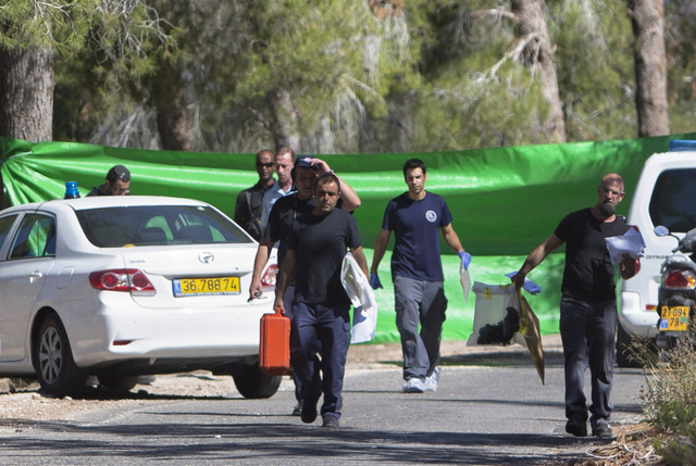 Israeli forensic police officers carry evidence bags in a forest in Jerusalem, Wednesday, July 2, 2014. Israeli police say Palestinians and Israeli forces have clashed following reports that an Ar ...