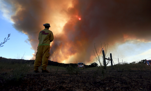 Smoke rises from the Butts Canyon Fire on Tuesday July 1, 2014, near Middletown, Calif., on the border between Lake and Napa counties. Crews are battling a raging wildfire that has burned more tha ...