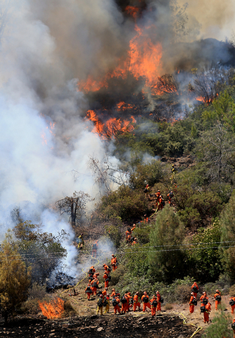 A crew heads back downhill as flames advance up a hillside on the Butts Canyon Fire, Tuesday, July 1, 2014, outside Middletown, Calif., on the border between Lake and Napa counties. By early eveni ...