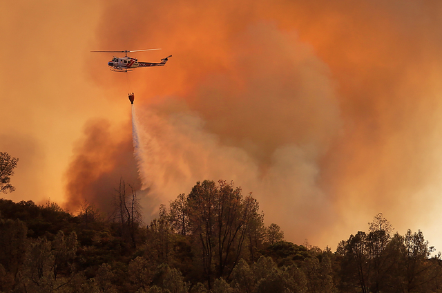 A Cal Fire helicopter makes a drop on the Butts Canyon Fire on Tuesday, July 1, 2014, near Middletown, Calif., close to the border between Lake and Napa counties. By early evening 140 homes were e ...