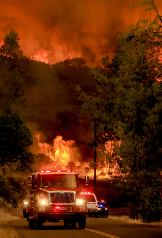 Fire personnel pull back from a wall of flames as it jumps Butts Canyon Road and Snell Valley Road, Tuesday, July 1, 2014, outside Middletown, Calif., near the border between Lake and Napa countie ...