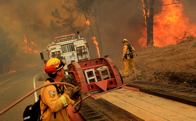 The Cal Fire helitack crew from Boggs Mountain puts out flames around a Cal Fire dozer transport as the Butts Canyon fire jumps Butts Canyon Road, Tuesday, July 1, 2014 . outside Middletown, Calif ...