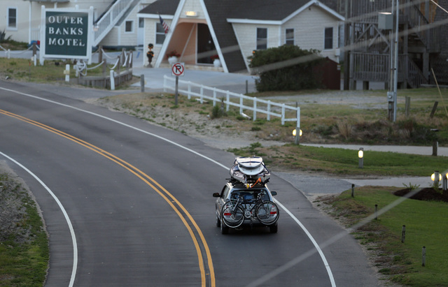 A car loaded down with bikes, kayaks and surfboards heads north on NC 12 through Buxton on Hatteras Island, N.C., at dawn on Thursday, July 3, 2014.  The island is under a mandatory evacuation ord ...
