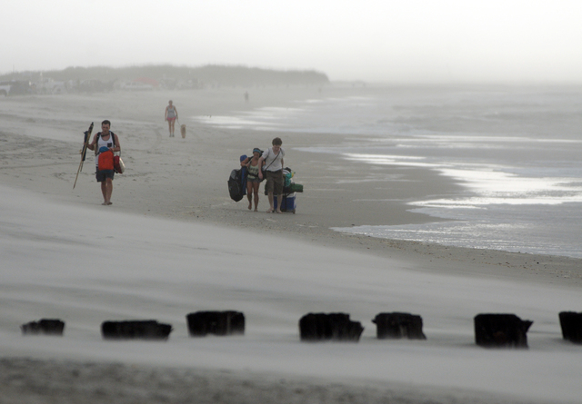 Clouds and rains move in as beachgoers leave Freeman Park at the north end of Carolina Beach, N.C., Thursday, July 3, 2014. Residents along the coast of North Carolina are bracing for the arrival  ...