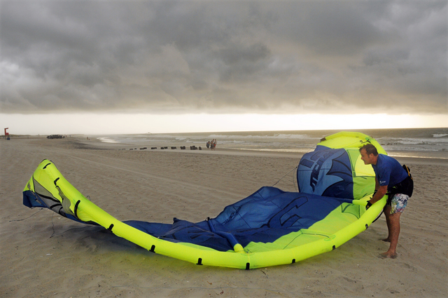 Kite boarder Pete Nero secures his kite as darks clouds and rain move in on the north end of Carolina Beach, N.C., Thursday, July 3, 2014. Residents along the coast of North Carolina are bracing f ...