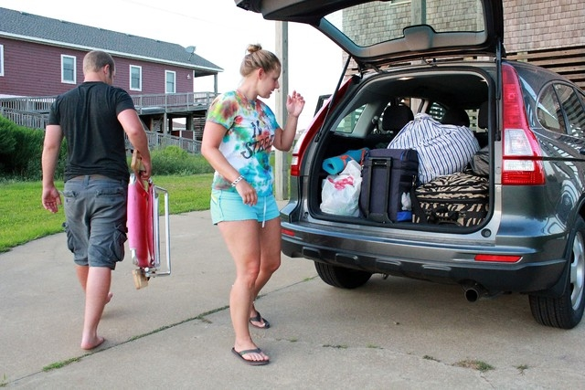 Nicole Specht, and and Ryan Witman, pack their Honda CRV heading back home to Lancaster Pa., before dawn on Thursday, July 3, 2014, during a mandatory evacuation, in Rodanthe, N.C. Arthur strength ...