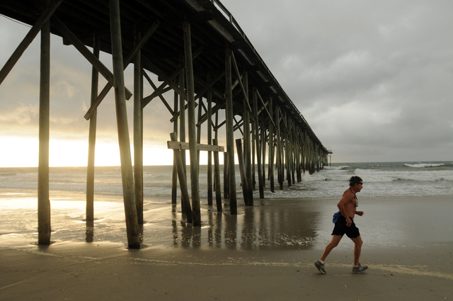 Clouds and rain move in as a man jogs along the shore of the north end of Carolina Beach, N.C., Thursday, July 3, 2014. Residents along the coast of North Carolina are bracing for the arrival of t ...