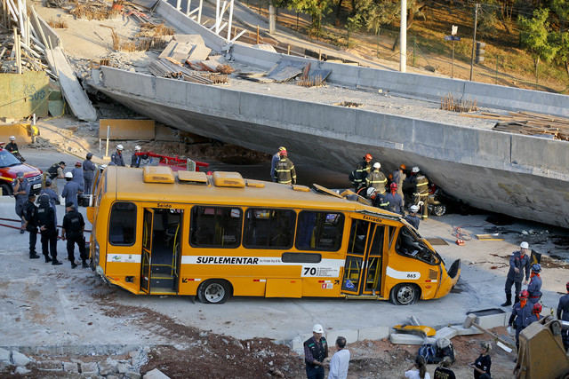 A bus sits damaged after a bridge collapsed in Belo Horizonte, Brazil, Thursday, July 3, 2014. The overpass under construction collapsed Thursday in the Brazilian World Cup host city. The incident ...
