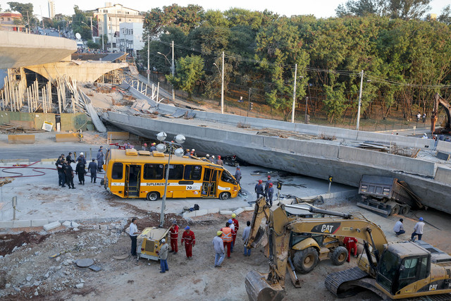 A bus sits damaged next to a bridge after it collapsed in Belo Horizonte, Brazil, Thursday, July 3, 2014. The overpass under construction collapsed Thursday in the Brazilian World Cup host city. T ...