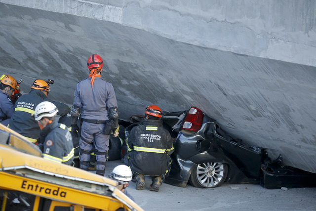 Fire department personnel work to retrieve a car pressed underneath a collapsed bridge in Belo Horizonte, Brazil, Thursday, July 3, 2014. The overpass under construction collapsed Thursday in the  ...