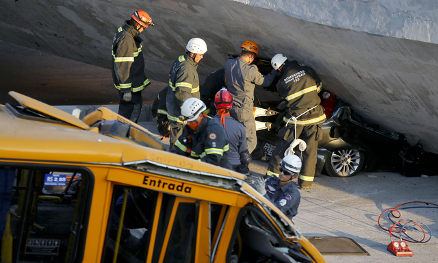 Fire department personnel work to retrieve a car from underneath a collapsed bridge in Belo Horizonte, Brazil, Thursday, July 3, 2014. The overpass under construction collapsed Thursday in the Bra ...