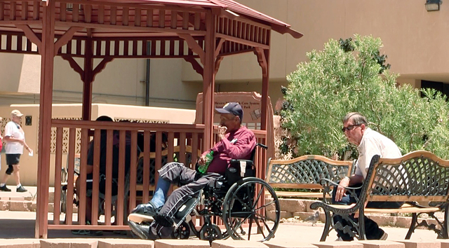 Men sit outside the Raymond G. Murphy VA Medical Center in Albuquerque, N.M., Thursday, July 3, 2014. A veteran who collapsed in an Albuquerque Veteran Affairs hospital cafeteria 500 yards from th ...