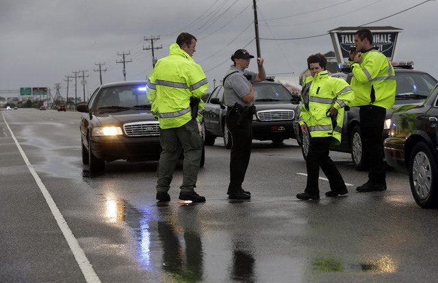 Police officers monitor an area of flooded road on Highway 64 as Hurricane Arthur passes through the area Friday, July 4, 2014, in Nags Head, N.C. (AP Photo/Gerry Broome)
