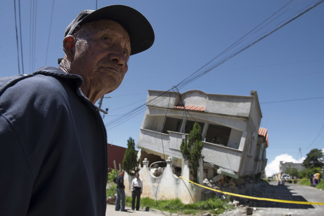 A man stands close to homes that collapsed during an earthquake in San Pedro, Guatemala, Monday, July 7, 2014. A magnitude-6.9 earthquake on the Pacific Coast jolted a wide area of southern Mexico ...