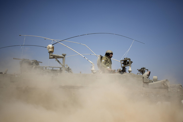 Israeli soldiers drive on an armored personal carrier near the Israel and Gaza Strip border, Monday, July 7, 2014. The Islamic militant group Hamas that rules Gaza vowed revenge on Israel for the  ...