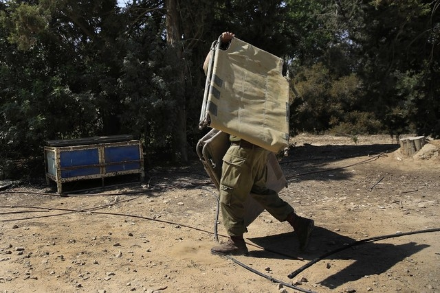 An Israeli soldier carries a bunk bed near the Israel Gaza border, Israel, Monday, July 7, 2014. The Islamic militant group Hamas that rules Gaza vowed revenge on Israel for the death of several o ...
