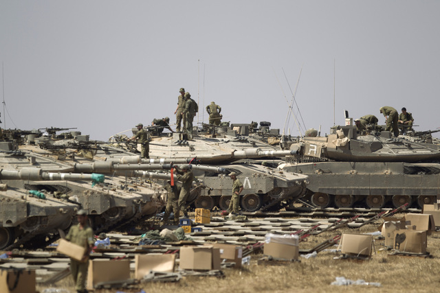 Israeli soldiers work on their tanks near the Israel and Gaza Strip border, Monday, July 7, 2014. The Islamic militant group Hamas that rules Gaza vowed revenge on Israel for the death of several  ...