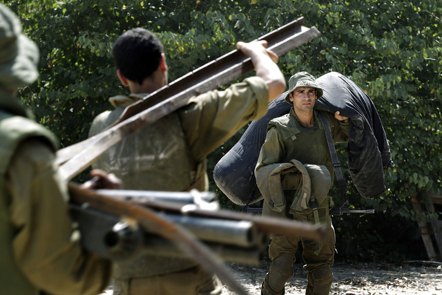 Israeli soldiers carry equipment near the Israel Gaza border, Israel, Monday, July 7, 2014. The Islamic militant group Hamas that rules Gaza vowed revenge on Israel for the death of several of its ...