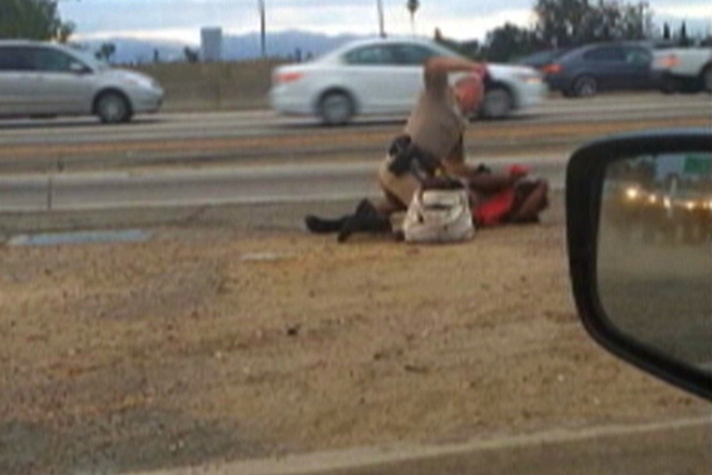 In this July 1, 2014 image made from video provided by motorist David Diaz, a California Highway Patrol officer straddles a woman while punching her in the head on the shoulder of a Los Angeles fr ...