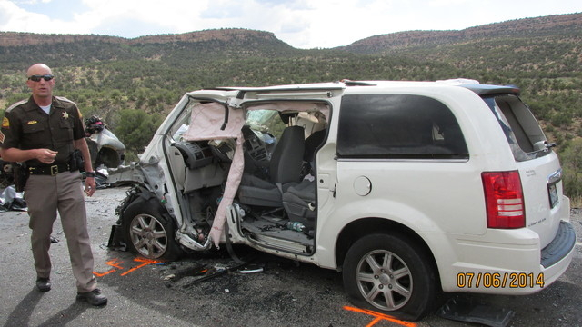 This photo provided by the Utah Department of Public Safety shows a damaged vehicle from a head-on collision, Sunday July 6, 2014, in southern Utah.  A van carrying five people was trying to pass  ...