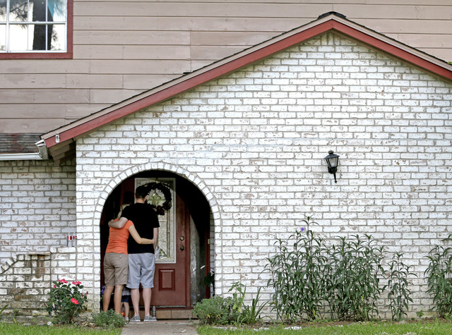 A family who identified themselves as friends of the victims, pause on the porch Thursday, July 10, 2014, after placing flowers and a framed photograph at the door of the home where a gunman kille ...