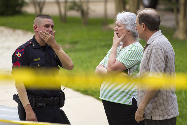 People stand with a law enforcement officer near the scene of a shooting Wednesday, July 9, 2014, in Spring, Texas. A Harris County Sheriff's Office statement says precinct deputy constables were  ...