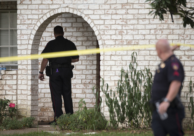 Law enforcement officers investigate the scene of a shooting Wednesday, July 9, 2014, in Spring, Texas. A Harris County Sheriff's Office statement says precinct deputy constables were called to a  ...