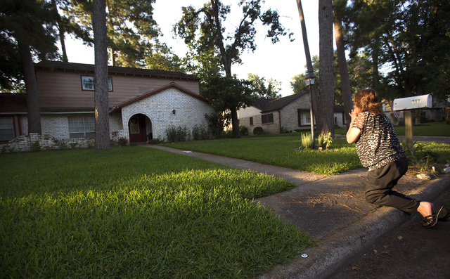 Patti Beller prays Thursday, July 10, 2014, in Spring, Texas, outside the home that was the scene of a multiple shooting the night before. The Harris County Sheriff's Office says Ronald Lee Haskel ...