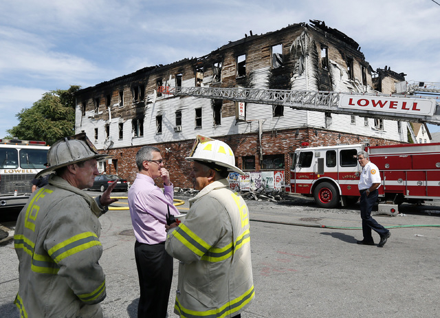 Fire officials observe the scene of a burned three-story apartment and business building in Lowell, Massachusetts, Thursday, July 10, 2014, where officials said seven people died in a fast-moving  ...