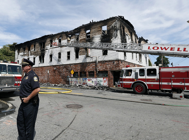 A policeman secures the scene of a burned three-story apartment and business building in Lowell, Massachusetts, Thursday, July 10, 2014, where officials said seven people died in a fast-moving pre ...