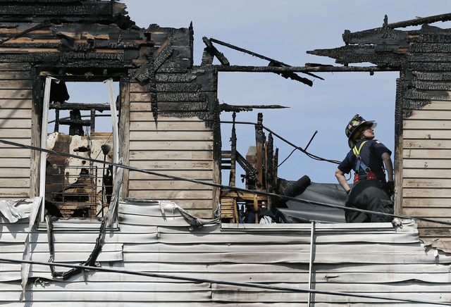 A firefighter works on the top floor inside a burned three-story apartment and business building in Lowell, Massachusetts, Thursday, July 10, 2014, where officials said seven people died in a fast ...