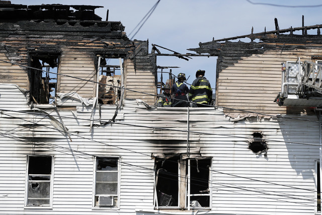 Firefighters work on the top floor inside a burned three-story apartment and business building in Lowell, Massachusetts, Thursday, July 10, 2014, where officials said seven people died in a fast-m ...
