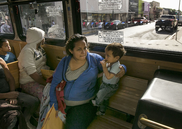 In this photo taken July 4, 2014, Marta Beltran, 19, of El Salvador, holds her 18-month-old son, Lenny, as they ride a city shuttle bus from the McAllen city bus station to the Sacred Heart Cathol ...