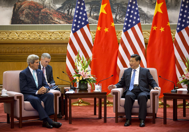 U.S. Secretary of State John Kerry, left, meets with Chinese President Xi Jinping, right, after attending the 6th U.S.-China Strategic and Economic Dialogue and 5th round of U.S. -China High Level ...