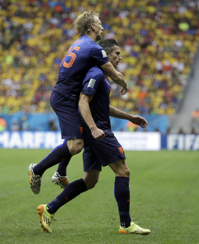 Netherlands' Robin van Persie, right, celebrates with his teammate Dirk Kuyt after scoring his team's first goal on a penalty shot during the World Cup third-place soccer match between Brazil and  ...