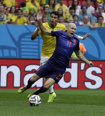 Netherlands' Arjen Robben, front, is tripped by Brazil's Thiago Silva during the World Cup third-place soccer match between Brazil and the Netherlands at the Estadio Nacional in Brasilia, Brazil,  ...