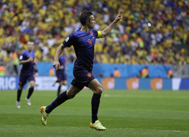 Netherlands' Robin van Persie celebrates after scoring his team's first goal on a penalty shot during the World Cup third-place soccer match between Brazil and the Netherlands at the Estadio Nacio ...