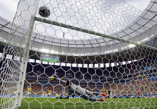 Brazil's goalkeeper Julio Cesar dives in an attempt to stop a shot by Netherlands' Robin van Persie, who scored his team's first goal on a penalty shot during the World Cup third-place soccer matc ...
