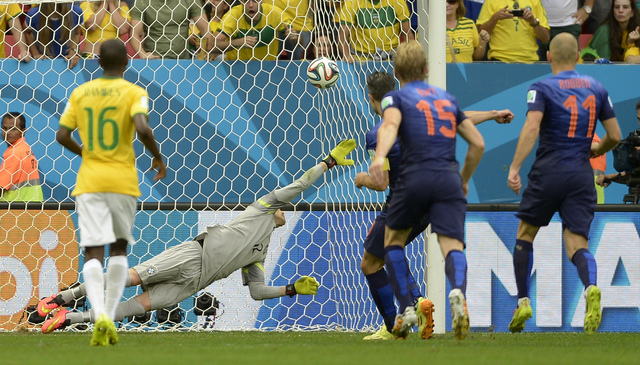 Netherlands' Robin van Persie, third right, scores the opening goal from the penalty spot during the World Cup third-place soccer match between Brazil and the Netherlands at the Estadio Nacional i ...