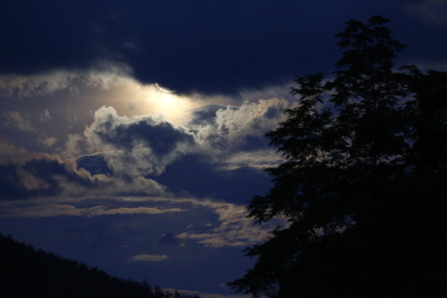 The full moon peeks through the clouds over forest near Sarajevo,Bosnia, Saturday, July 12, 2014. The so-called super moon appeared up to 14 percent larger than normal as it's orbit is at it's clo ...