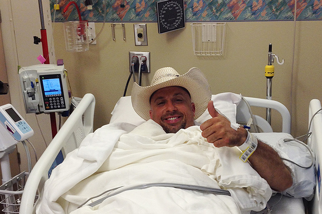 In this photo taken Saturday July 12, 2014, injured rodeo promoter Frank Koloski gives a thumbs up from his bed at Providence Medical Center in Anchorage, Alaska. Koloski was gored by a bull Satur ...