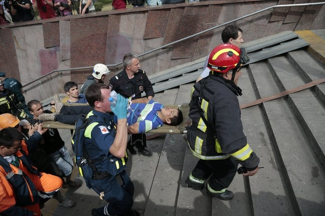 Paramedics, a police officer and a volunteer carry an injured man out from a subway station after a rush-hour subway train derailment in Moscow on Tuesday, July 15, 2014. The accident killed 20 pe ...