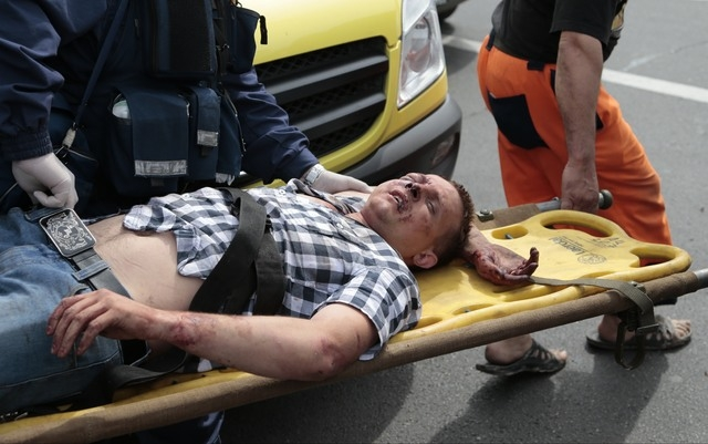 Paramedics carry an injured man out from a subway station after a rush-hour subway train derailment in Moscow on Tuesday, July 15, 2014. The accident killed 20 people and injuring at least 150, em ...