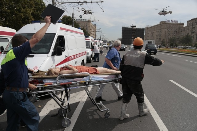Paramedics carry an injured man out from a subway station after a rush-hour subway train derailment, to be transported by a medical helicopter in Moscow on Tuesday, July 15, 2014. Twenty people we ...