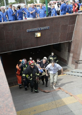 Paramedics, a police officer and a volunteer carry an injured man out from a subway station after a rush-hour subway train derailment in Moscow on Tuesday, July 15, 2014. Twenty people were killed ...