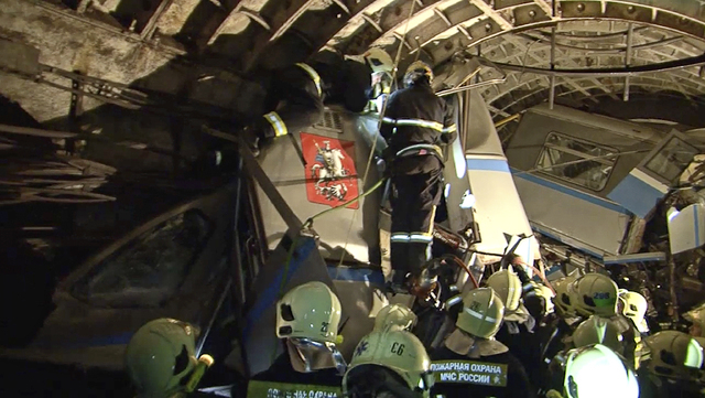 A frame grab from video provided by the Russian Ministry for Emergency Situations shows rescue teams working inside the tunnel where several cars of the wrecked train look almost coiled, occupying ...