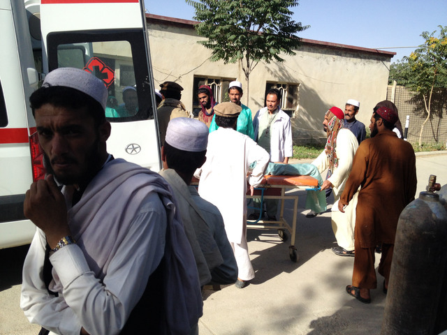 A wounded man is helped who was injured when a suicide bomber detonated his explosives-packed vehicle near a crowded market and a mosque, at the main hospital in Sharan, capital of Paktika provinc ...