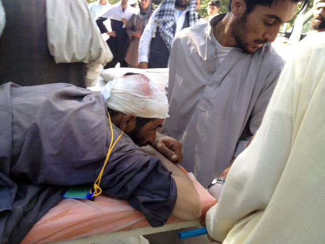 A wounded man is helped at the main hospital in Sharan, Afghanistan, who was injured when a suicide bomber detonated his explosives-packed vehicle near a crowded market and a mosque, in Urgun, Afg ...
