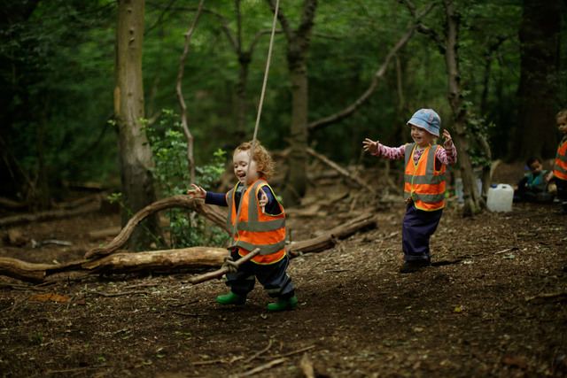 "In this photo taken Tuesday, July 8, 2014, Olive, left, and Matilda play with a rope swing at the ""Into the Woods"" outdoor children's nursery in Queen's Wood, in the Highgate area of nor ..."